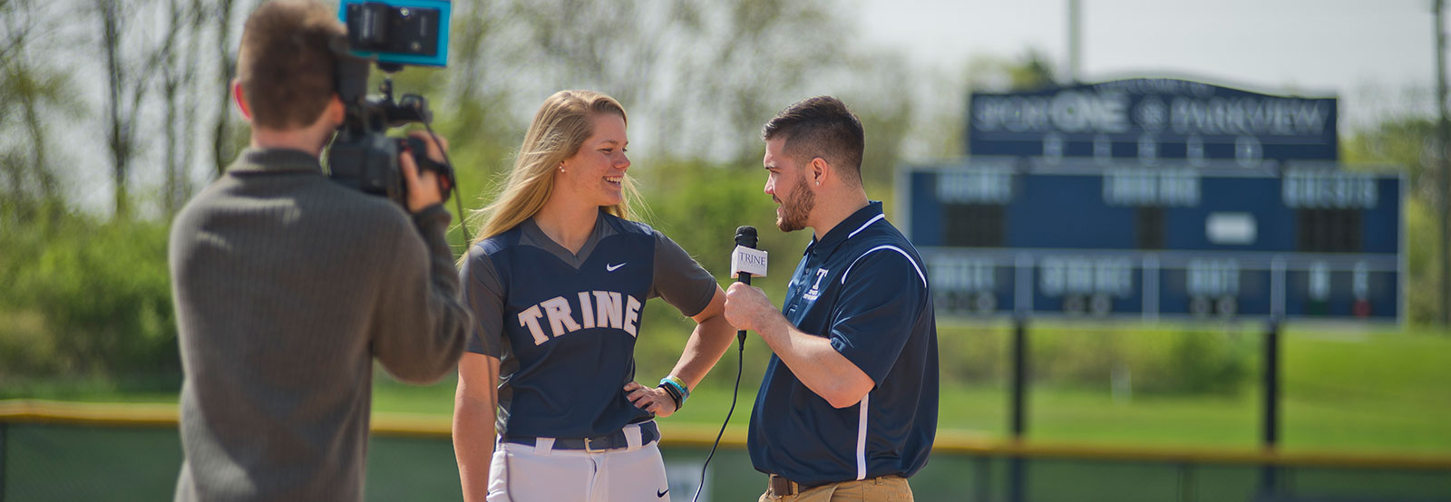 Student interviewing a softball player